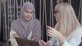 Due donne stanno discutendo il progetto di funzionamento che guardano in taccuino in ufficio stock footage