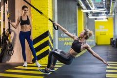 Due donne stanno esercitando con il sistema del trx a loro volta immagini stock