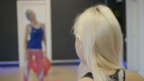 Due donne stanno facendo gli esercizi di riscaldamento in palestra moderna, stante di fronte ad a vicenda stock footage