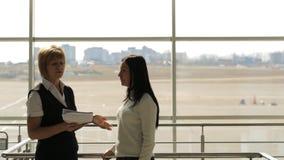 Due donne stanno parlando nel corridoio aspettante dell'aeroporto archivi video