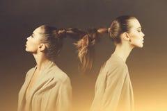 Due donne sveglie con capelli lunghi legati nella treccia immagini stock