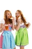 Due donne vestite bavaresi che mangiano le ciambelline salate Fotografie Stock Libere da Diritti