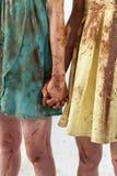 Due donne in vestiti sporchi hanno guastato congiuntamente con cioccolato Fotografie Stock