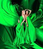 Due donne in vestito verde con capelli e cuori lunghi Fotografie Stock Libere da Diritti