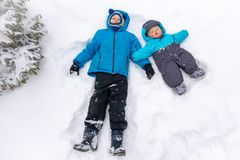 Due 8 e 0 anni dei ragazzi, bugia in un cumulo di neve bianco pulito vicino all'abete rosso immagine stock libera da diritti