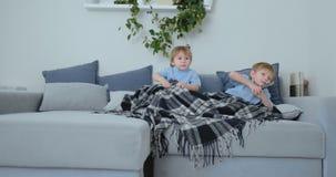 Due 4 e 2 anni dei ragazzi, stanno guardando la TV sedersi sullo strato Una manifestazione di TV emozionante Fumetti di vista stock footage