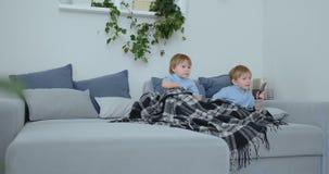 Due 4 e 2 anni dei ragazzi, stanno guardando la TV sedersi sullo strato Una manifestazione di TV emozionante Fumetti di vista I b stock footage