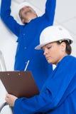 Due elettricisti nella sala in costruzione immagini stock