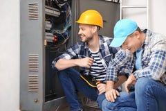 Due elettricisti vicino al quadro di distribuzione all'interno fotografia stock