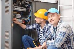 Due elettricisti vicino al quadro di distribuzione all'interno immagini stock