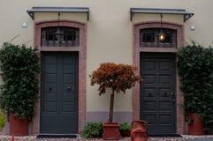 Due entrate in una casa a terrazze con un giardino, immagini stock