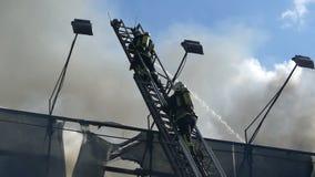 Due eroi su una scala metallica estinguono il fuoco con acqua archivi video