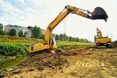 Due escavatori gialli che scavano sul letto Fotografia Stock