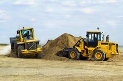 Due escavatori muovono la terra su un sito di costruzione della r Fotografia Stock