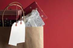Due etichette in bianco e una borsa in pieno dei regali fotografie stock libere da diritti