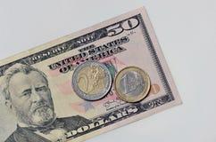 Due euro monete su 50 dollari Fotografie Stock Libere da Diritti