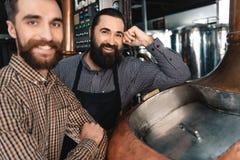 Due fabbricanti di birra barbuti felici stanno il contenitore vicino in cui la birra è fatta fermentazione brewery fotografia stock libera da diritti