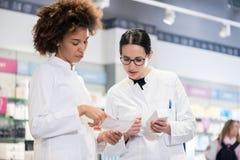 Due farmacisti che confrontano le medicine per quanto riguarda le indicazioni e gli effetti collaterali immagine stock