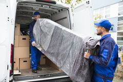 Due fattorini che scaricano mobilia dal veicolo fotografia stock
