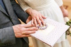 Due fedi nuziali dorate a disposizione accessori per la sposa e lo sposo Preparazione per la cerimonia Fotografie Stock Libere da Diritti