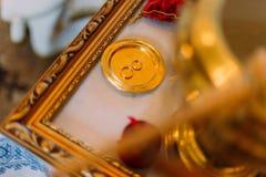 Due fedi nuziali dorate nel bown cerimoniale sull'altare della chiesa con la scultura Immagini Stock Libere da Diritti