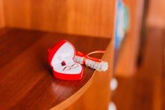 Due fedi nuziali dorate in scatola in forma di cuore con il rotolo sveglio hanno stilizzato come note musicali al backgr di legno Fotografia Stock