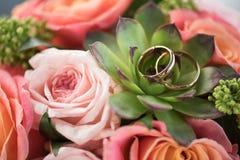 Due fedi nuziali dorate sul mazzo sulle rose e sul succulente Immagine Stock Libera da Diritti