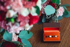 Due fedi nuziali dorate in una scatola arancio Fotografie Stock