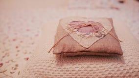 Due fedi nuziali su un piccolo cuscino Preparazione per una cerimonia, dettagli di nozze nello stile rustico destra del cursore video d archivio
