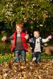 Due felici, fratelli sorridenti che giocano in prateria di autunno Immagini Stock