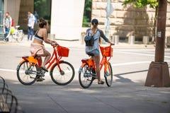 Due femmine attraenti sulle bici locative fotografia stock