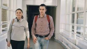 Due femminili e gli studenti maschii stanno camminando nel corridoio dell'università che discutono qualcosa Incontrano gli amici  stock footage