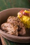 Due fette di filetto di carne di maiale sul piatto dell'argilla con le patate Fotografie Stock