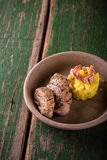Due fette di filetto di carne di maiale sul piatto dell'argilla con le purè di patate Fotografia Stock