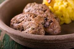 Due fette di filetto di carne di maiale sul piatto e sulle patate dell'argilla Fotografia Stock Libera da Diritti
