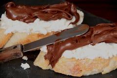 Due fette di pane, formaggio di ricotta e crema spalmabile di cacao e delle nocciole Fotografie Stock