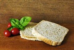 Due fette di pane tostato, fatte dall'intero pasto, su un piatto di legno con una foglia di basilico e di alcuni pomodori Fotografia Stock Libera da Diritti