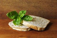 Due fette di pane tostato, fatte dall'intero pasto, su un piatto di legno e su una foglia di basilico in uno studio Fotografia Stock
