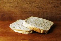 Due fette di pane tostato, fatte dall'intero pasto, su un piatto di legno in uno studio Fotografie Stock