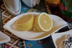 Due fette di piatto giallo del limone Limone tagliato dentro a met? Le due metà del limone che si trova sul piatto immagine stock