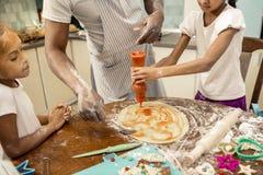 Due figlie sveglie che aiutano il loro padre che cucina pizza per pranzo immagine stock