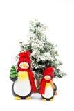 Due figurine del pinguino con l'albero di Natale nell'inverno Fotografia Stock