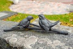 Due figurine dell'uccello sopra una pietra tombale Fotografie Stock