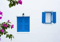 Due finestre blu sulla costruzione bianca della parete immagini stock