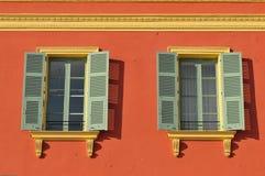 Due finestre con le tonalità di finestra si aprono su una parete rossa Immagini Stock