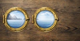 Due finestre della nave con l'isola tropicale dell'oceano o del mare Immagini Stock Libere da Diritti