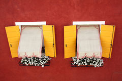 Due finestre gialle identiche sulla parete rossa Immagine Stock Libera da Diritti