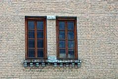 Due finestre marroni su un muro di mattoni grigio di un edificio residenziale Immagine Stock
