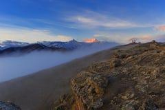 Due fotografi e un cane incontrare l'alba nelle montagne fotografia stock libera da diritti