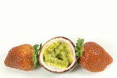 Due fragole e un frutto della passione affettato su bianco Fotografia Stock